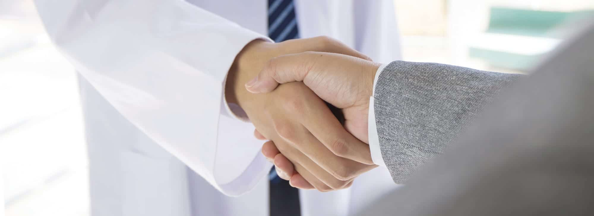 Medical professional and sales representative shaking hands
